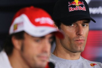 Mark Webber looks at championship leader Fernando Alonso at yesterday's press conference