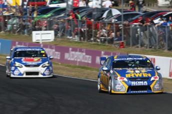 Lee Holdsworth leads Tim Slade at Queensland Raceway
