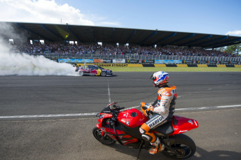 Stoner watches his V8 Supercar in action from the seat of a production Honda motorcycle at February's Top Gear Festival